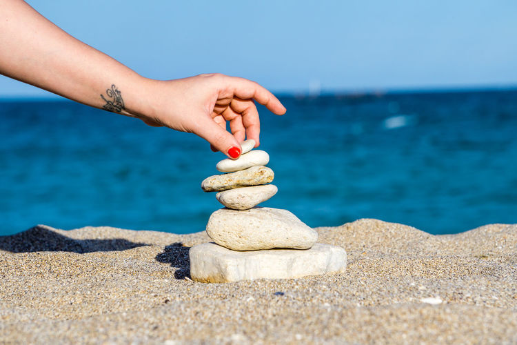 Cropped hand of woman stacking stones at beach against sea