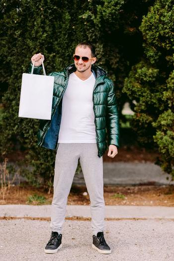 Full length of man wearing sunglasses holding shopping bag standing outdoors
