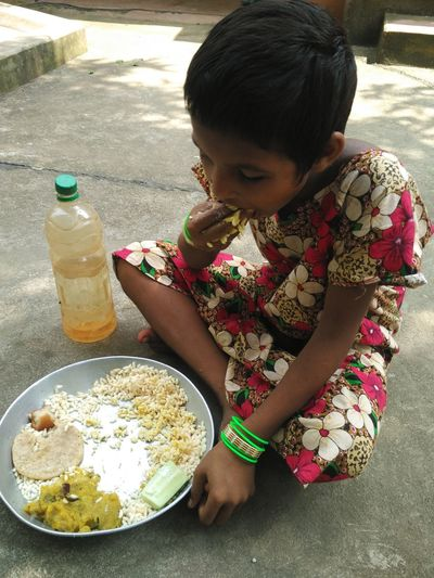 High Angle View Of Girl Eat7ing Food While Sitting On Footpath