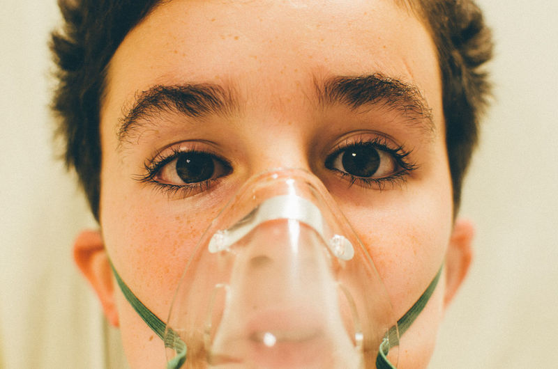Close-Up Portrait Of Boy Wearing Oxygen Mask