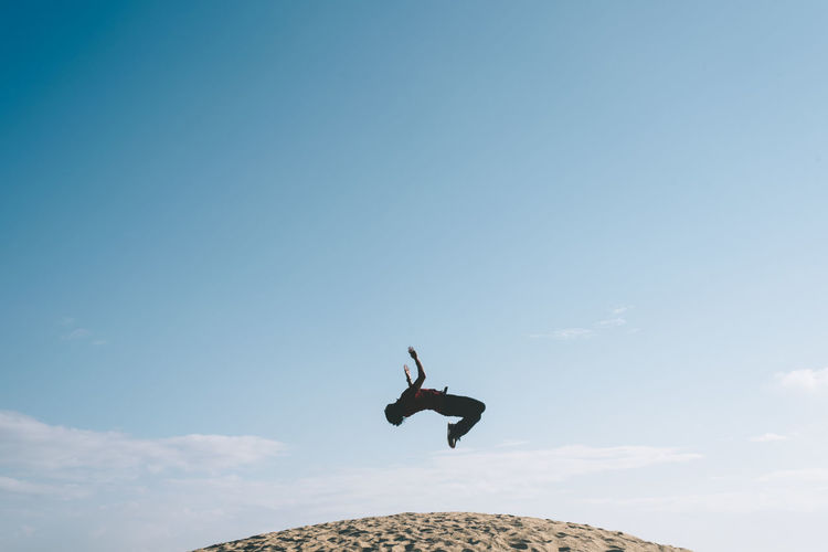 Low angle view of man jumping against sky
