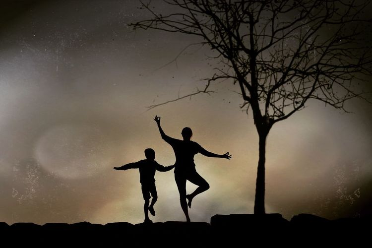 Silhouette men standing on tree against sky
