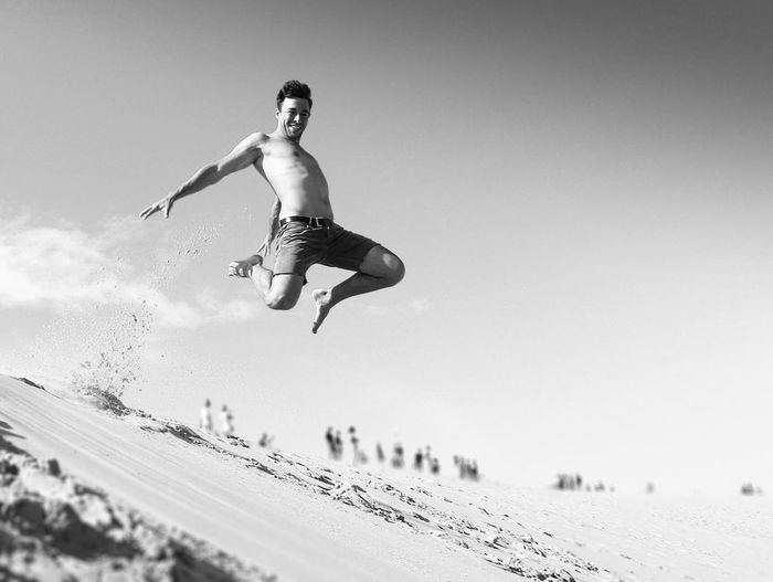 Full Length Of Shirtless Man Jumping On Beach Against Clear Sky