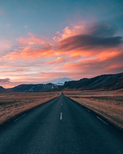 Empty road leading towards mountains against cloudy sky during sunset