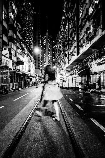Man walking on illuminated street amidst buildings at night