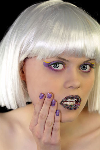 Close-up portrait of young woman in purple make-up