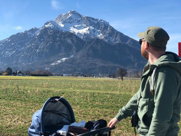 Man with baby stroller standing against mountain