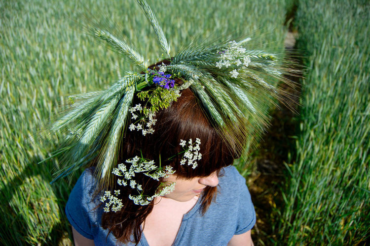High angle view of plants on woman head in farm during sunny day