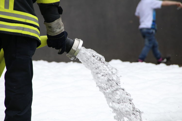 Midsection of man holding fire hose while standing on land