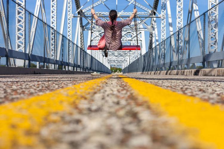 Surface level of woman swinging on bridge