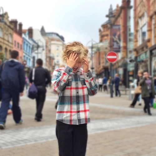 Annoyed boy standing on street in city