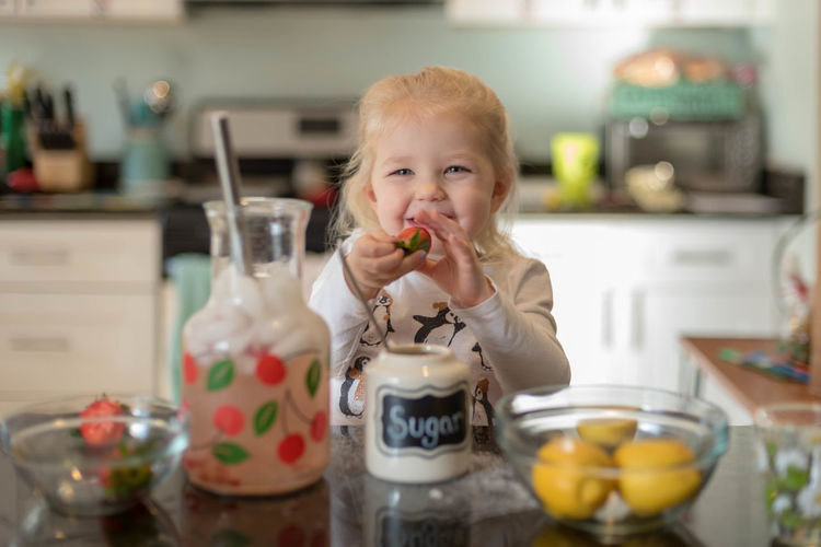 Cute blonde girl making homemade fresh squeezed strawberry lemonade at the kitchen counter - hands on learning Helping Home Lemonade Strawberries Blond Hair Childhood Counter Cute Expression Face Family With One Child Food And Drink Fresh Squeezed Freshness Indoors  Ingredients For Italian Cooking Kids In The Kitchen Kitchen Lemons Lifestylephotographer Little Girl Made With Love Making Preschooler Real People