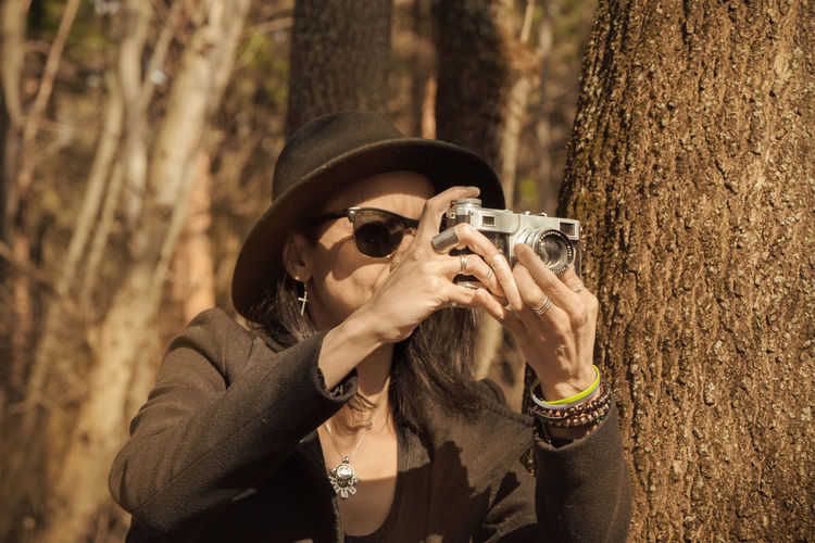 Woman photographing near tree trunk