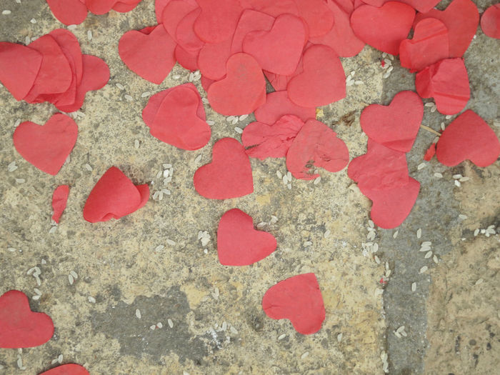 rice and red hearts strewn on the pavement Petal Outdoors Heart Shape No People Full Frame Red High Angle View Textured  Positive Emotion Love Multi Colored Day Close-up Backgrounds Marram Grass Decoration Symbolism