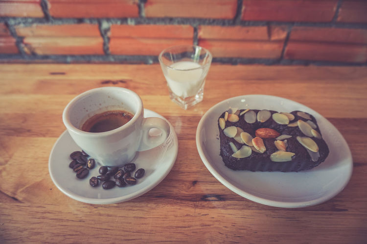 High angle view of coffee cup and dessert on table