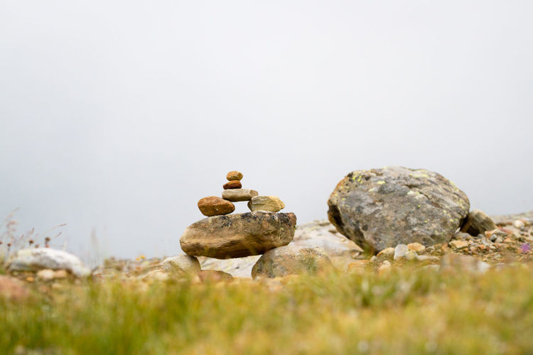 Rock Solid Rock - Object Nature No People Copy Space Day Tranquility Beauty In Nature Selective Focus Stone - Object Land Outdoors Stack Plant Stone Tranquil Scene Grass Sky Pebble Manmade Tradition Sign Alps