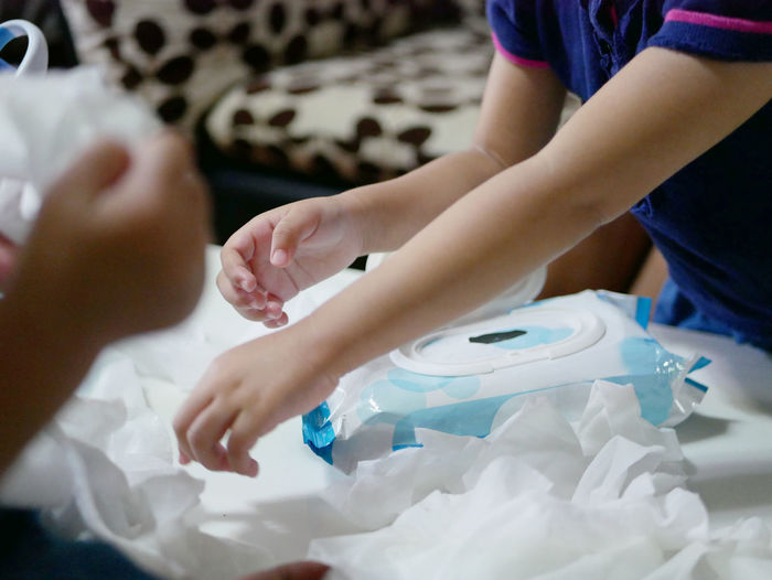 Midsection of children playing with tissue papers