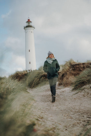 Woman walking in front of lighthouse Lighthouse Protection Full Length Security Architecture Built Structure Land Tower One Person Sky Guidance Building Exterior Nature Leisure Activity Safety Direction Standing Lifestyles Real People Outdoors