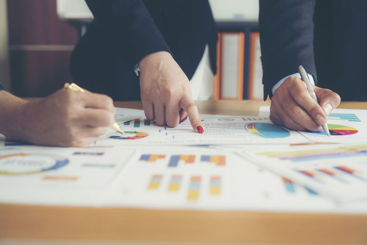 Close-up of businessman and colleague working over graph on table
