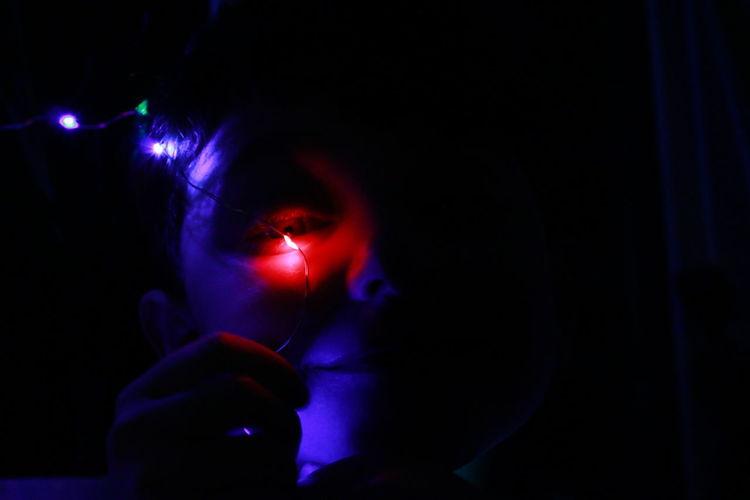 Close-up portrait of boy holding illuminated lighting equipment in darkroom