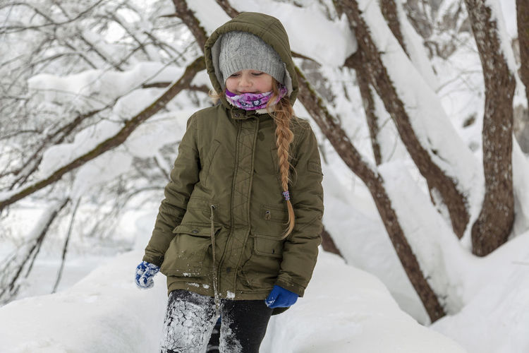 Full length of child standing on snow covered field
