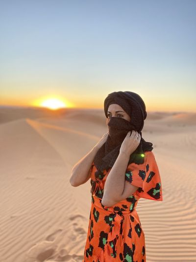 Woman wearing scarf while standing in desert against sky during sunset
