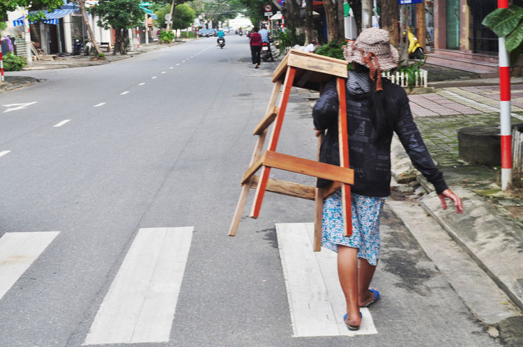 Woman carrying wooden stool in street in Da Nang, Vietnam. Carrying Chairs Da Nang Day Lifestyles Loads Outdoors Pedestrian Crossings Real People Rear View Street Sun Hats Transportation Vietnam Walking Weight Women Wooden Furniture