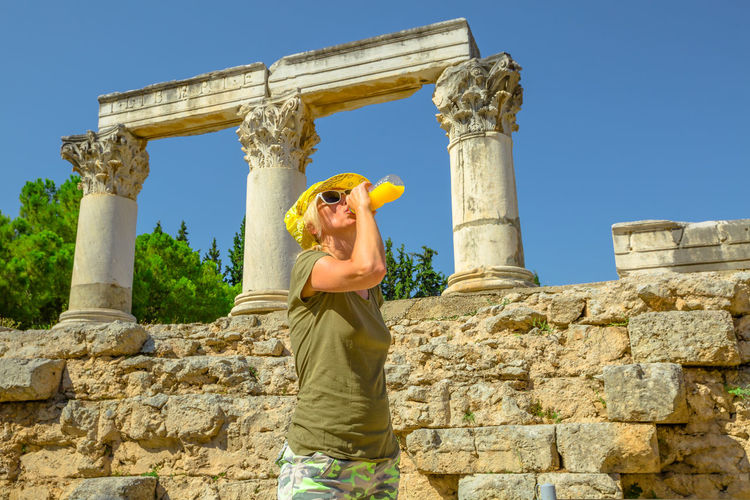 Low angle view of woman having drink against damaged columns