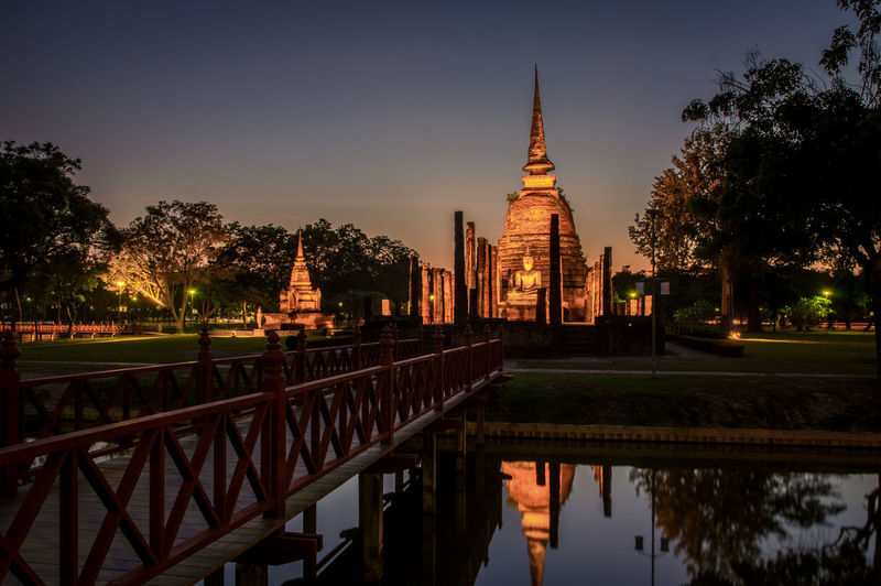 Buddha Buddhist Temple Built Structure Architecture Tree Sky Building Exterior Water Plant Religion Belief Place Of Worship Reflection Building Spirituality Nature Lake Illuminated No People Travel Destinations Outdoors Thailand
