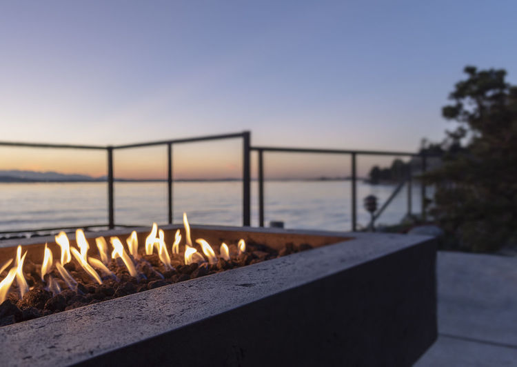 Backyard gas lit fire pit at golden hour blue hour sunset by the waters edge. copy space, no people.