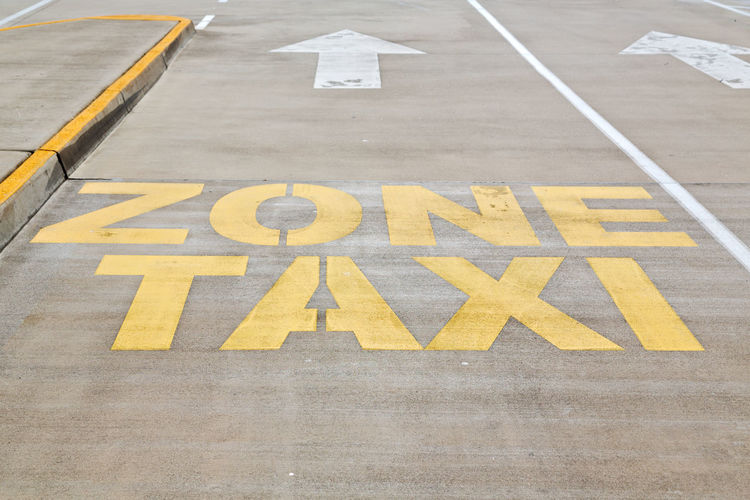 Taxi Sign Road Information Traffic Asphalt Background Transport Signal Urban Symbol Street City Mark Yellow Concept Paint Detail Safety Driver Pavement Public Object Bus Place Lane Drive Caution Restriction Taxicab Travel White Horizontal Way Queue Gray Control Infrastructure Cab Text Vehicle LINE STAND Closeup Outdoors Station Black Zone Sidewalk Arrow