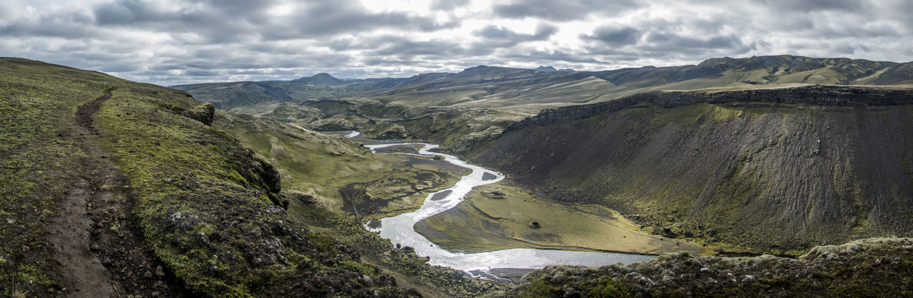Panoramic image of river flowing mountains against sky