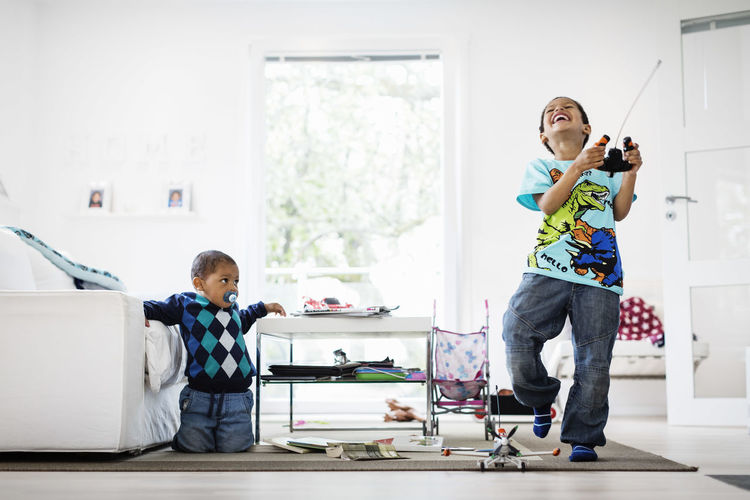 Full length of boy standing on mobile phone at home