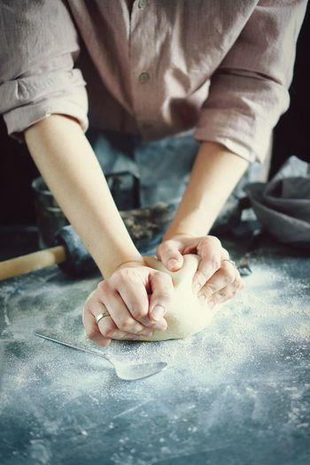 Midsection of woman kneading dough in kitchen