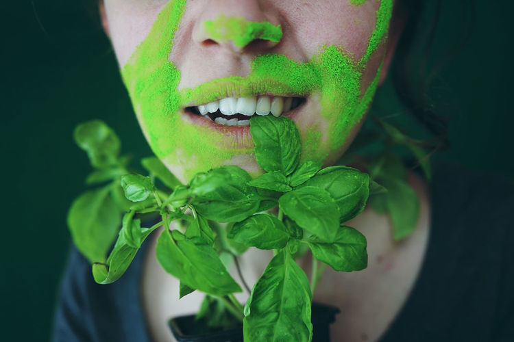 Close-up midsection of woman with face paint eating basil leaf