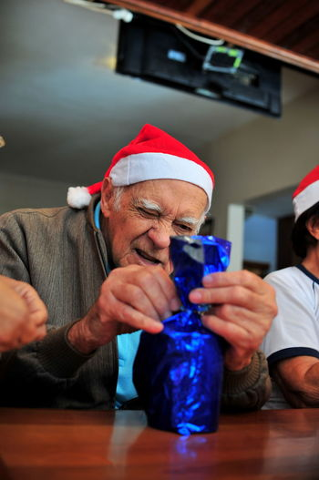 Senior man packing christmas present on table