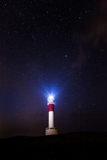 Illuminated lighthouse against sky at night