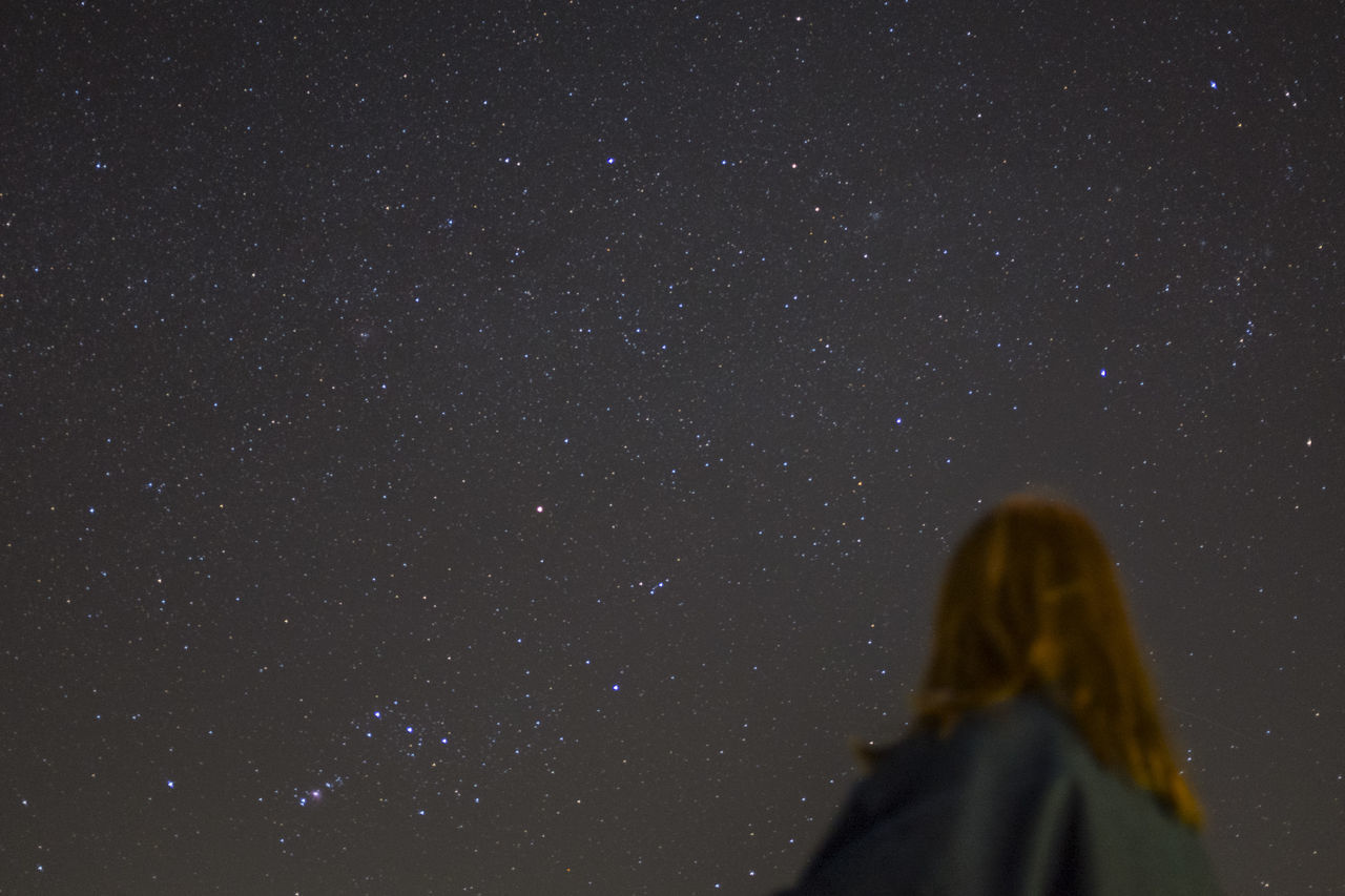 Low Angle View Of Woman Against Star Field At Night