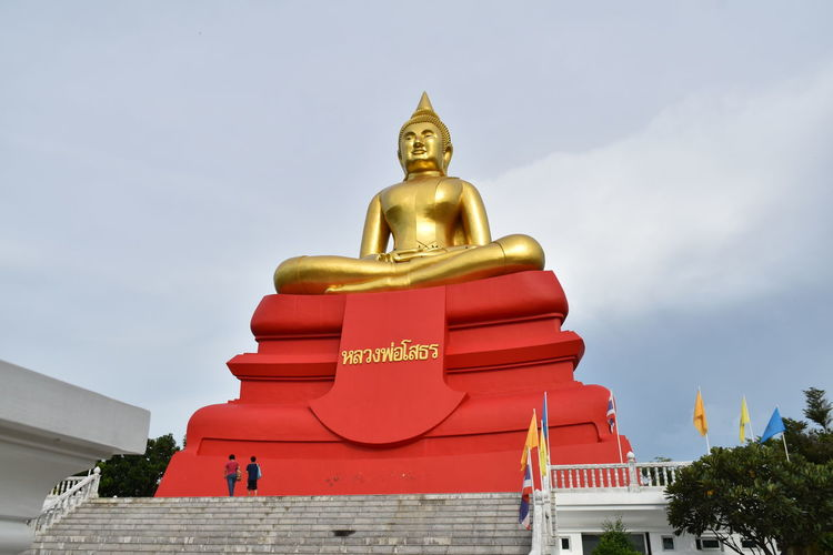 Low Angle View Of Gold Buddha Statue Against Sky