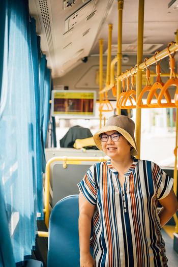 Portrait of smiling woman standing in bus