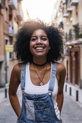 Smiling Woman Standing Against Buildings