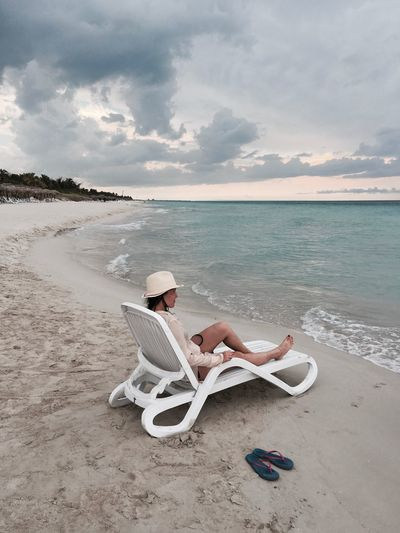 High angle view of woman sitting on deck chair at beach