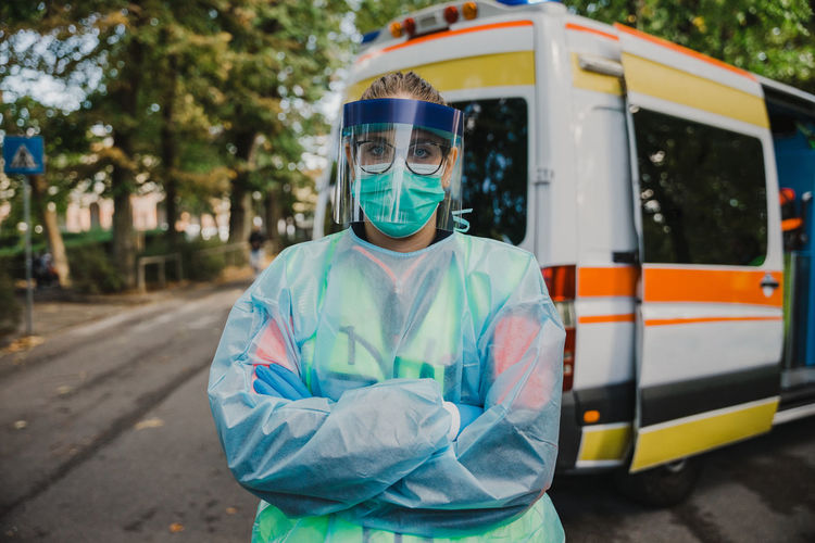 Portrait of doctor wearing protective suit standing against ambulance