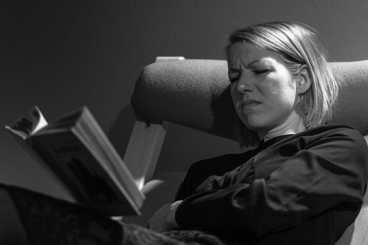 Tensed mid adult woman reading book while sitting on chair at home
