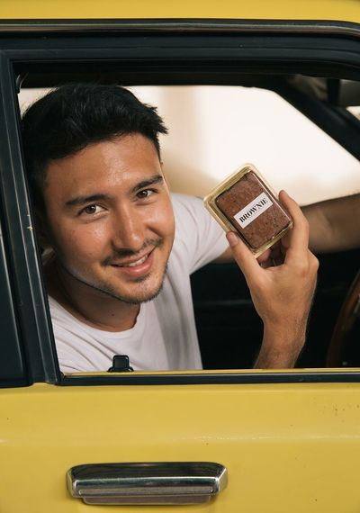 Portrait of young man showing food while sitting in car