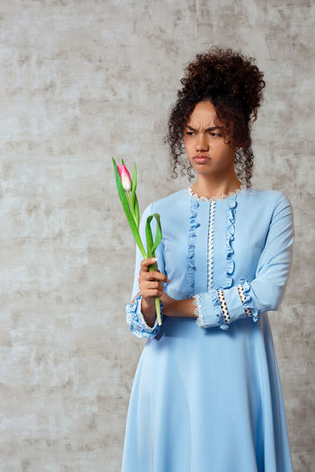 Young woman holding tulip while standing against wall