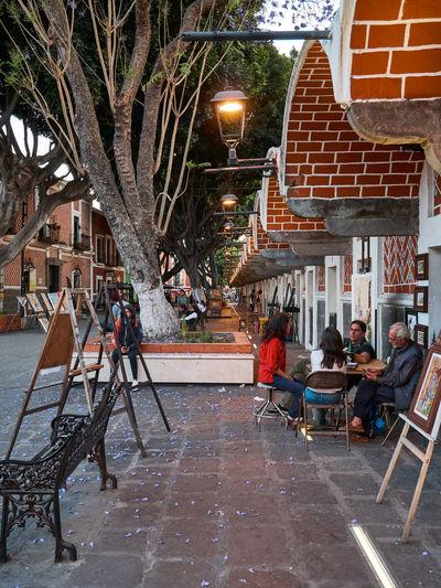People sitting on sidewalk cafe against buildings in city