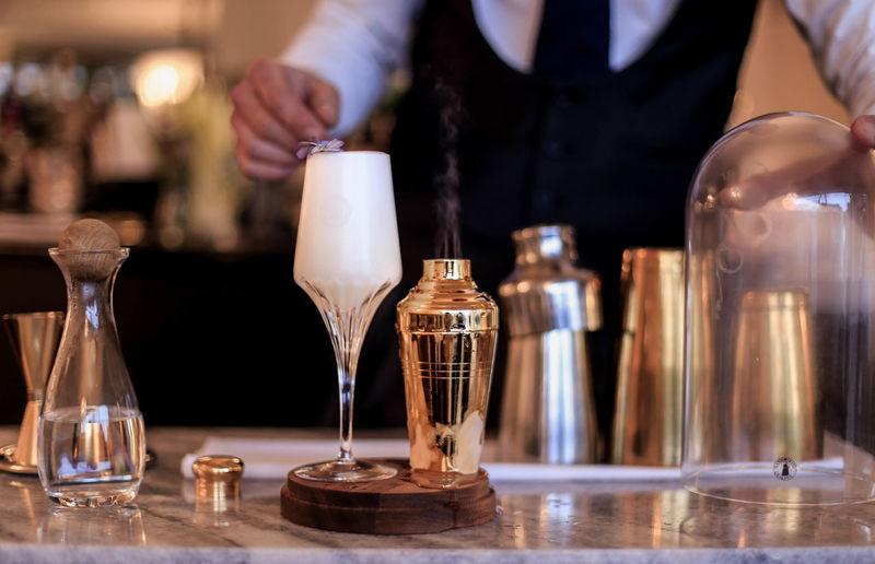 Close-Up Of Bar Tender Preparing Drink At Table