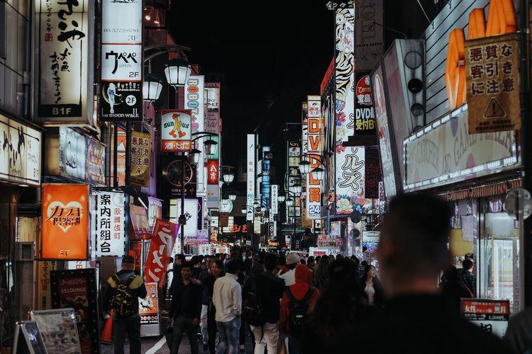 People on illuminated street in city at night