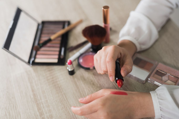 Cropped Image Of Woman Testing Lipsticks On Hand At Table